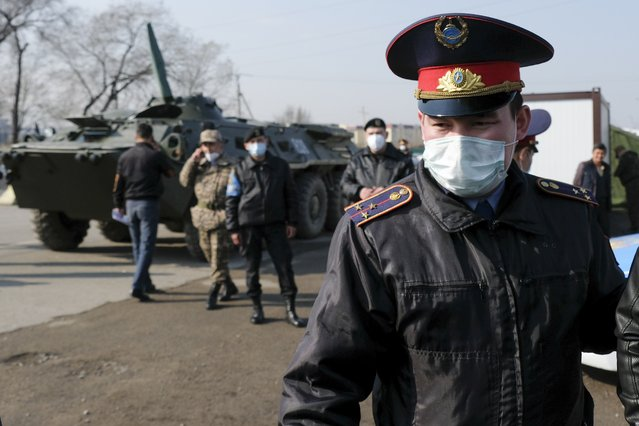 Armed Kazakhstan police wearing face masks block an area in Almaty, Kazakhstan, Thursday, March 19, 2020. A residential block in Almaty, Kazakhstan's former capital and largest city, has been surrounded by the military and blocked for entry and exit after one of the residents was diagnosed with the new coronavirus. (Photo by Vladimir Tretyakov/AP Photo)
