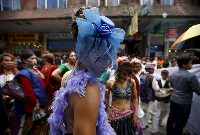 A reveller (C) dances while taking part in a LGBT (lesbian, gay, bisexual, and transgender) pride parade to mark Gaijatra Festival, also known as the festival of cows, in Kathmandu, Nepal, August 30, 2015. (Photo by Navesh Chitrakar/Reuters)