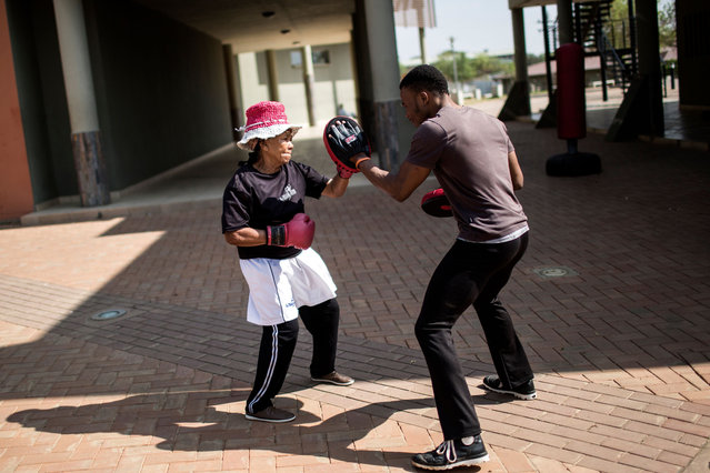 "Gladys Ngwenya of The ""Boxing Gogos"" (Grannies) is pictured sparring with a trainer during a session hosted by the A Team Gym in Cosmo City in Johannesburg on September 19, 2017. (Photo by Gulshan Khan/AFP Photo)"