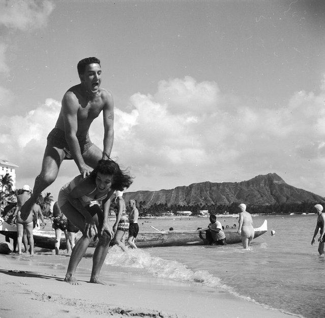 Bert and Ellie Lang, a young American couple on their honeymoon in Hawaii play leap-frog on Honolulu's Waikiki beach. In the background is the extinct volcanic crater of Diamond Head, circa 1955. (Photo by Orlando)