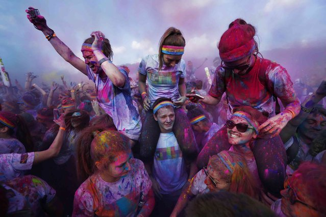 Participants at Sydney's Color Run are covered in multi-colored dyes thrown into the air, August 24, 2014. Inspired by the Hindu Holi festival, participants take part in a five kilometer long run dotted with locations where colored powders are thrown in a carnival atmosphere. (Photo by Jason Reed/Reuters)