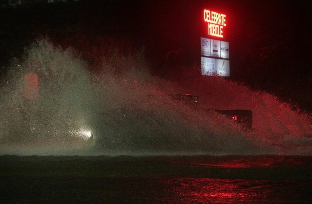 A large truck drives through a flooded Water St. in downtown Mobile, Ala., during Hurricane Nate, Sunday, October 8, 2017, in Mobile, Ala. (Photo by Brynn Anderson/AP Photo)