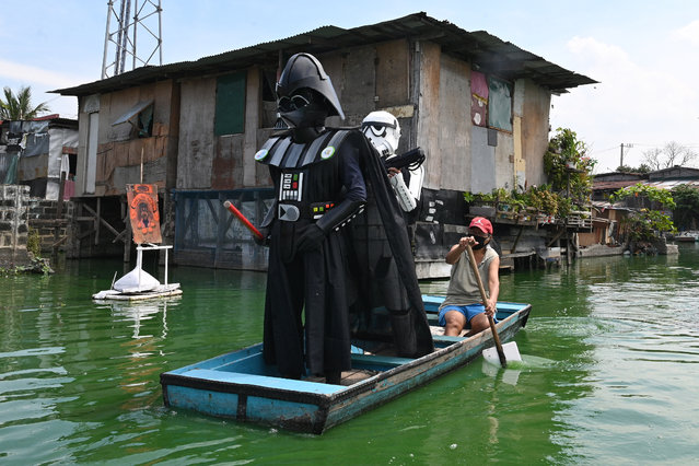 Local youth representatives dressed a Stormtrooper and Darth Vader (L-in black) from the Star Wars film franchise patrol in a wooden boat around a submerged village to remind residents to stay at home during the enhanced community quarantine in suburban Manila on May 6, 2020, as part of government's efforts to combat the spread of the COVID-19 coronavirus. (Photo by Ted Aljibe/AFP Photo)