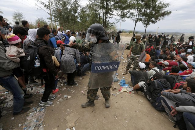 Macedonian policemen tryto impose order as hundreds of refugees and migrants wait to cross Greece's border with Macedonia, near the Greek village of Idomeni, September 7, 2015. (Photo by Yannis Behrakis/Reuters)