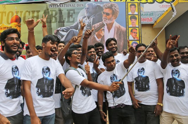 "Fans of Indian superstar Rajinikanth take a selfie outside a cinema hall to celebrate the screening of ""Kabali"" in Chennai, India, Friday, July 22, 2016. Private companies declared a holiday and parents kept children out of school as an air of celebration swept southern India for the premiere of Rajinikanth's latest film. Hundreds of thousands of Rajinikanth fans thronged cinemas across Tamil-language India and Malaysia to catch the pre-dawn showing of ""Kabali"", a gangster movie that left patrons jumping from their seats and dancing in the aisles at the sight of their hero. (Photo by Aijaz Rahi/AP Photo)"