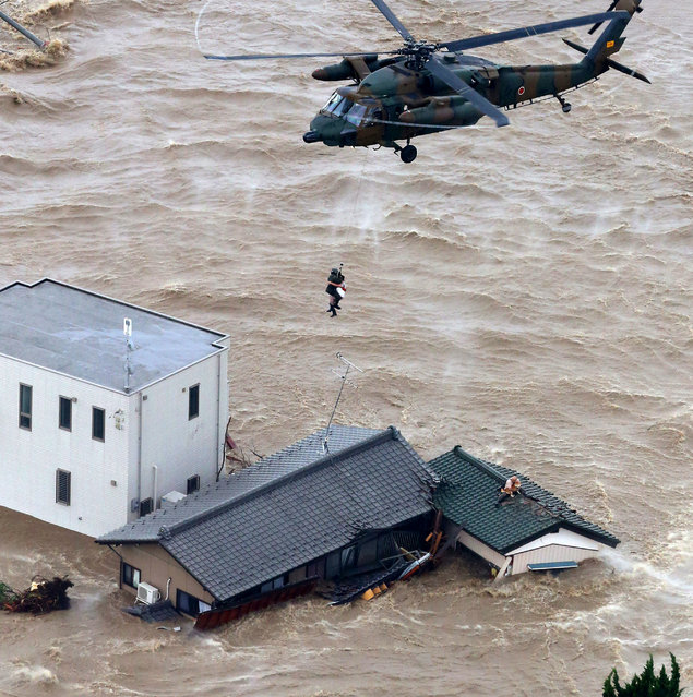 A resident is rescued from a flooded residential area in Joso, Ibaraki prefecture, northeast of Tokyo Thursday, September 10, 2015. (Photo by Kyodo News via AP Photo)