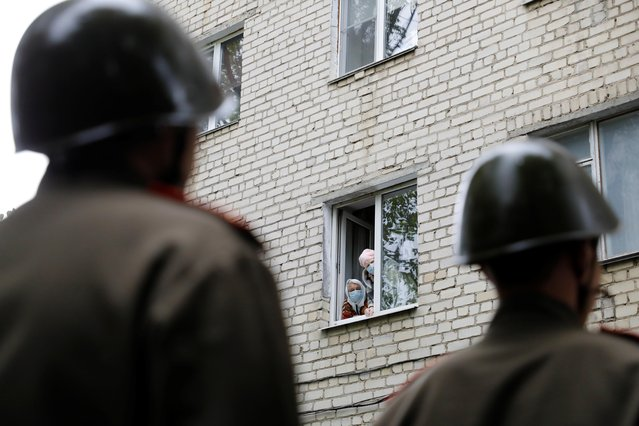Local residents wearing protective face masks look out of the window during a military parade organized personally for World War Two veteran Pavel Zakharchenko, who participated in the Battle of Berlin, ahead of the Victory Day celebrations, amid the coronavirus disease (COVID-19) outbreak in Stavropol, Russia on May 8, 2020. (Photo by Eduard Korniyenko/Reuters)