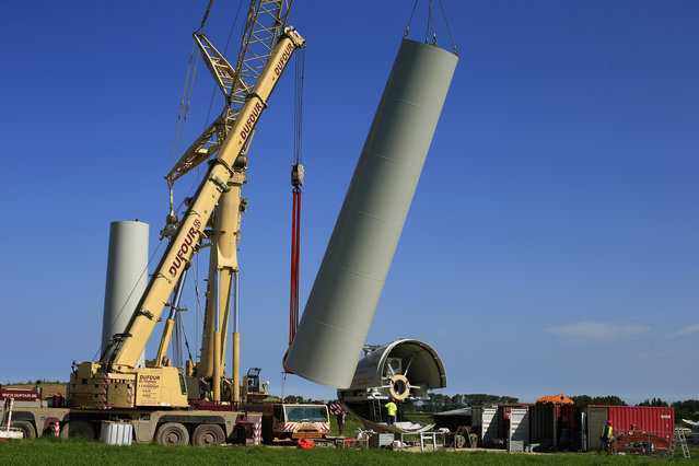 A crane lifts a tower section of a turbine in Meneslies, France July 17, 2014. (Photo by Benoit Tessier/Reuters)