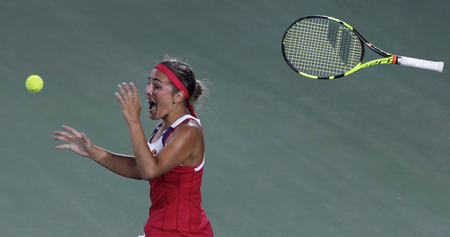 Monica Puig, of Puerto Rico, tosses her racquet and celebrates after winning the gold medal against Angelique Kerber, of Germany, during the final round at the 2016 Summer Olympics in Rio de Janeiro, Brazil, Saturday, August 13, 2016. (Photo by Charles Krupa/AP Photo)