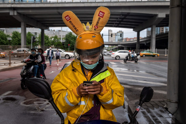 A delivery man looks at a map on his smartphone along a street in Beijing on May 25, 2020. (Photo by Nicolas Asfouri/AFP Photo)