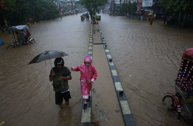 A boy makes his way through a flooded area as he returns from school during heavy monsoon rains in Gauhati, Assam state, India, Monday, September 22, 2014. Officials say relentless rains in parts of northeastern India have triggered landslides and flash floods, killing at least seven people. (Photo by Anupam Nath/AP Photo)