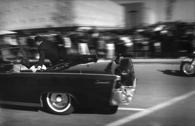 In this November 22, 1963 file photo, the limousine carrying mortally wounded President John F. Kennedy races toward the hospital seconds after he was shot in Dallas. Secret Service agent Clinton Hill is riding on the back of the car, Nellie Connally, wife of Texas Gov. John Connally, bends over her wounded husband, and first lady Jacqueline Kennedy leans over the president. (Photo by Justin Newman/AP Photo/File)