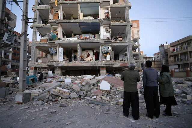 In this photo provided by the Iranian Students News Agency, ISNA, people look at destroyed buildings after an earthquake at the city of Sarpol-e-Zahab in western Iran, Monday, November 13, 2017. (Photo by Pouria Pakizeh/ISNA via AP Photo)