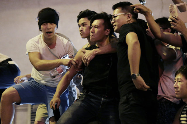 Angry protesters confront each other in Kowloon's crowded Mong Kok district, Saturday, October 4, 2014 in Hong Kong. Clashes broke out Friday as Hong Kong residents and pro-Beijing supporters tried to force pro-democracy activists from the streets they were occupying, reviving the possibility that the weeklong standoff could turn violent despite and attempt by the city's leader to defuse the situation. (Photo by Wong Maye-E/AP Photo)