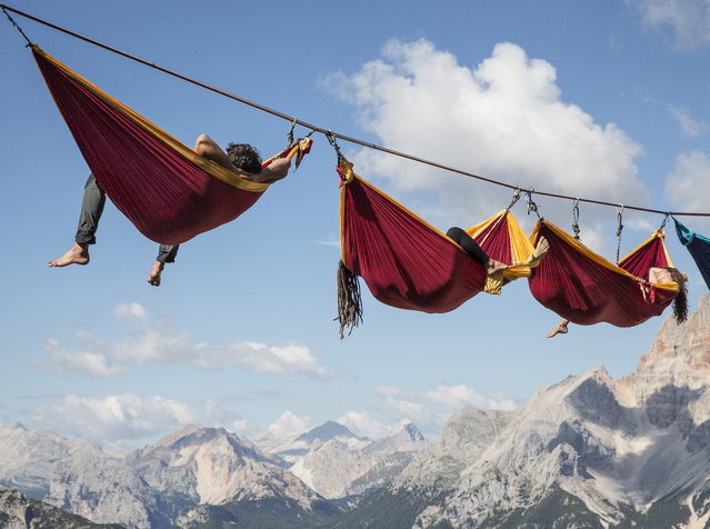 Doesn't taking a nap in a hammock outdoors sound lovely? Perhaps not when you're hanging in the air, thousands of feet above ground, between two mountains in the Italian Alps! Which is exactly what these adventurous folks did during the International Highline Meeting in Monte Piana, Italy. (Photo by Sebastian Wahlhuetter Photography)