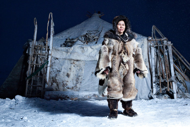 """""""Woman of Chukotka"""". Reindeer herder standing in front of winter yurt in traditional clothing made of reindeer skin in Chukotka. Photo location: Russia. (Photo and caption by Sasha Leahovcenco/National Geographic Photo Contest)"""