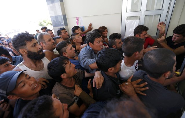 Migrants wrestle to buy train ticket at the train station in Beli Manastir, Croatia September 18, 2015. (Photo by Laszlo Balogh/Reuters)