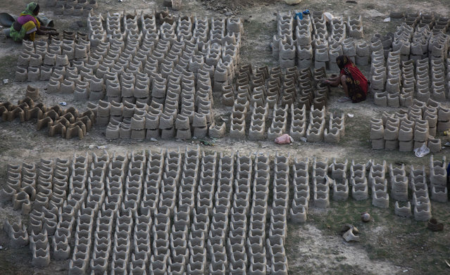 """In this Tuesday, November 7, 2017, file photo, Indian women prepare clay stoves to be sold to devotees arriving for the upcoming """"Magh Mela"""" festival in Allahabad, India.  Hundreds of thousands of Hindus are expected to take holy dips at the confluence of Ganges and Yamuna rivers during the astronomically auspicious period of over 45 days celebrated as Magh Mela, that begins later this month. (Photo by Rajesh Kumar Singh/AP Photo)"""