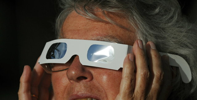 A woman wears special glasses to view the solar eclipse from the beach at Palm Cove in Australia's Tropical North Queensland on November 14, 2012. Eclipse-hunters have flocked to Queensland's tropical northeast to watch the region's first total solar eclipse in 1,300 years on November 14, which occurred as the moon passed between the earth and the sun, casting a shadow path on the globe and lasting for a maximum on the Australian mainland of 2 minutes and 5 seconds. (Photo by Greg Wood/AFP Photo)