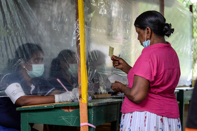An election official (L) behind a plastic sheet checks the identification card of a voter during a mock election to test the guidelines implemented against the COVID-19 coronavirus in Ingiriya of Kalutara District in Western Province on June 14, 2020. Sri Lanka will hold parliamentary elections on August 5, more than three months late because of the coronavirus, the election commission said June 10 after health authorities gave their approval. A mock election will be held this weekend to test new health measures that will be implemented at polling booths and counting centres, commission chairman Mahinda Deshapriya said. (Photo by Lakruwan Wanniarachchi/AFP Photo)
