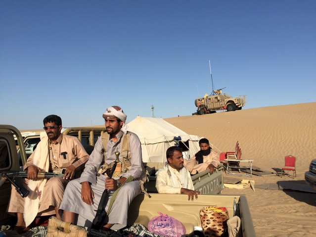 Yemeni tribesmen sit on the back of a pick-up truck near a military base in the Yemeni frontline province of Marib September 14, 2015. Gulf Arab coalition forces fighting Houthi militia in Yemen are advancing on the capital in a two-pronged offensive, generals told reporters on Monday at a desert oil compound they have turned into a military base. (Photo by Noah Browning/Reuters)