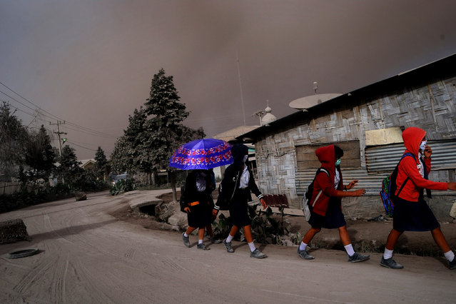School children wear face masks to protect from of volcanic ash following the eruption of Mount Sinabung volcano seen from Karo district on October 9, 2014. (Photo by Sutanta Aditya/AFP Photo)