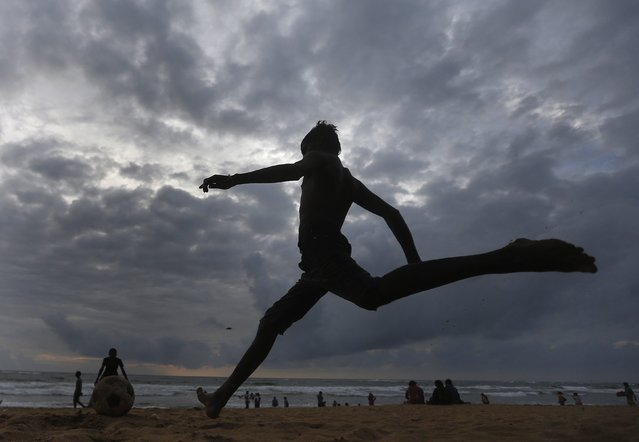 A boy runs to kick a soccer ball on the beach in Colombo September 10, 2014. (Photo by Dinuka Liyanawatte/Reuters)