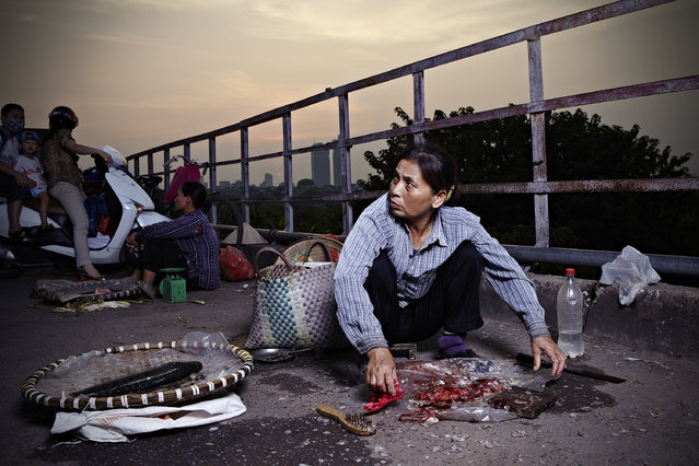 """Catch of the Day"". The sun was setting as a woman on Long Bien bridge hastily gutted and sold fresh fish to commuters on their way home. Photo location: Hanoi, Vietnam. (Photo and caption by Alexander Savvas/National Geographic Photo Contest)"