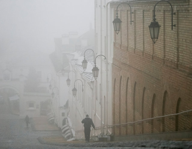 A man walks in fog in the territory of the Kiev Pechersk Lavra monastery in Kiev, Ukraine, December 1, 2017. (Photo by Gleb Garanich/Reuters)