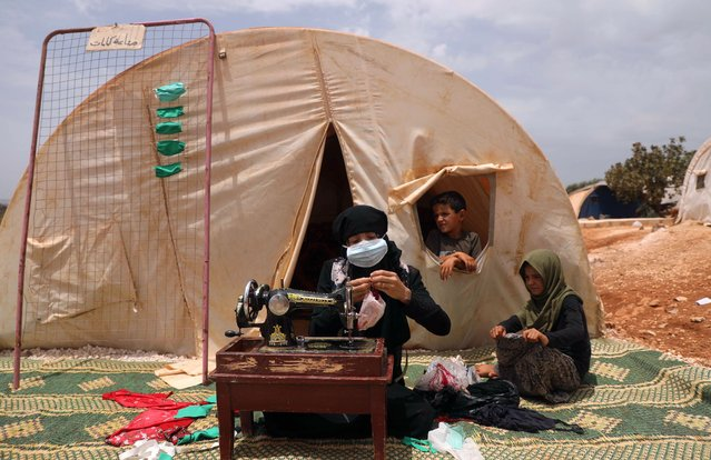 Thirty-years old displaced Syrian woman Umm Hussein sews protective face masks at a camp for the internally displaced people near the town of Maaret Misrin in Syria's northwestern Idlib province on July 27, 2020 amid the COVID-19 pandemic crisis. (Photo by Aaref Watad/AFP Photo)