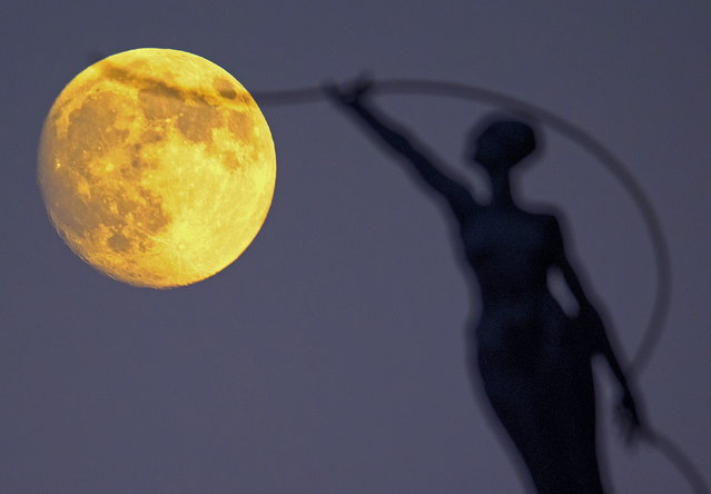 """A statue is seen silhouetted against the moon in Brussels, Belgium September 26, 2015. On Saturday, a perigee moon coincided with a full moon creating a """"supermoon"""" when it passed by the earth at its closest point, local media reported. (Photo by Yves Herman/Reuters)"""
