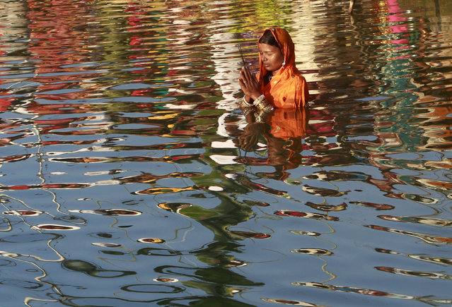 A woman worships the Sun god Surya in the waters of the Laxmi Narayan lake during the Hindu religious festival of Chatt Puja in Agartala October 29, 2014. (Photo by Jayanta Dey/Reuters)