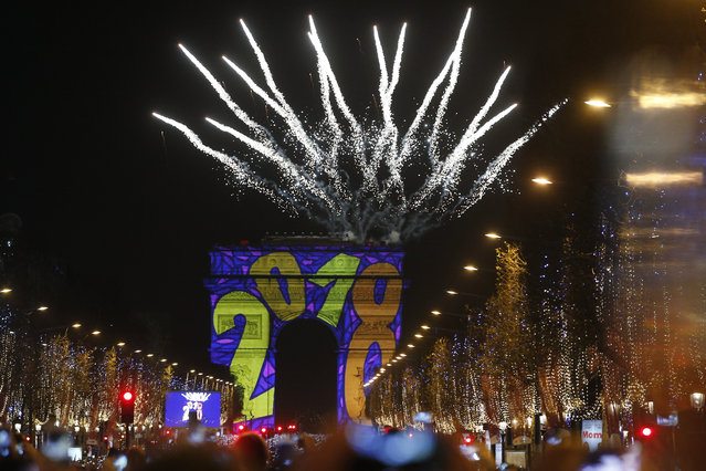 A firework explodes over the Arc de Triomphe as part of the New Year celebrations on the Champs Elysees, in Paris, France, Monday, January 1, 2018. (Photo by Thibault Camus/AP Photo)