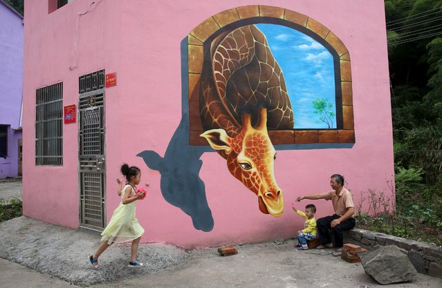 Tourists play in front of a 3D painting on the wall of a house in Luoyuan village, Jinhua, Zhejiang province, August 26, 2015. The village hired a team to put on 3D paintings all over the valley as a method to attract tourists and improve the income of local villagers, according to local media. (Photo by Reuters/China Daily)