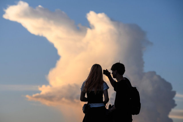A couple take photos in front of a view of a cloud as the sun sets in Hong Kong on July 21, 2020. (Photo by Anthony Wallace/AFP Photo)