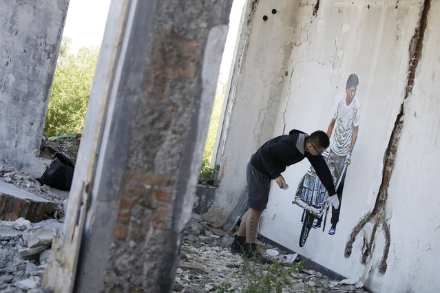 Chinese artist ROBBBB pastes his work on a wall in the ruins of a building in Beijing October 1, 2015. (Photo by Jason Lee/Reuters)