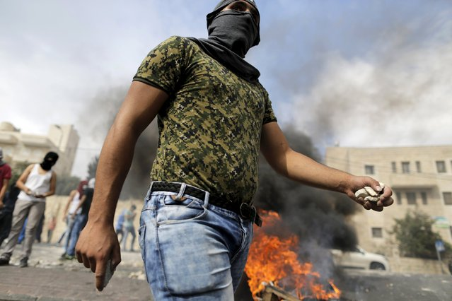 A masked Palestinian holds stones during clashes with Israeli police in Sur Baher, a village in the suburbs of Arab east Jerusalem, October 7, 2015. (Photo by Ammar Awad/Reuters)