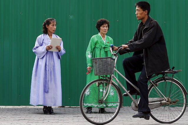 A man rides a bicycle past women wearing traditional clothes in downtown Pyongyang, North Korea October 8, 2015. (Photo by Damir Sagolj/Reuters)