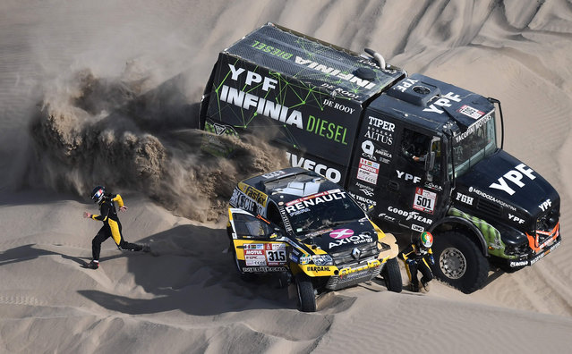 Renault' s Portuguese driver Carlos Souza (R) and French co- driver Pascal Maimon run for safety as Iveco' s Argentine truck driver Federico Villagra, co- driver Ricardo Torlaschi and mechanic Adrian Yacopini ride past during the 2018 Dakar Rally Stage 5 between San Juan De Marcona and Arequipa in Peru, on January 10, 2018. Sebastien Loeb was forced to pull out of the Dakar Rally after a back injury suffered by his co- driver in a disastrous fifth stage won by defending champion Stephane Peterhansel. (Photo by Franck Fife/AFP Photo)