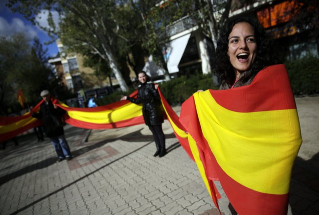 Spanish unionists shout slogans and hold a Spanish flag during a protest in Madrid against the symbolic independence vote in Catalonia November 9, 2014. Secessionist-minded politicians helped by cultural organisations and thousands of volunteers organised a symbolic independence vote in the autonomous community of Catalonia after Spain's High Court issued an injunction preventing a formal but non-binding referendum. (Photo by Andrea Comas/Reuters)
