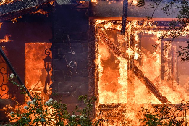 Flames from a wildfire consume a home in Anaheim Hills, Calif., Monday, October 9, 2017. Wildfires whipped by powerful winds swept through Northern California sending residents on a headlong flight to safety through smoke and flames as homes burned. (Photo by Jeff Gritchen/The Orange County Register via AP Photo)