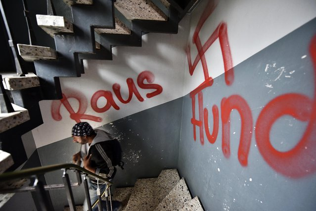 "A migrant walks the stairway in a refugee housing block  in Waltrop, western Germany, painted with a swastika graffiti and a writing ""get out dogs,"" Tuesday, October 13, 2015. Unknown persons sprayed extremist anti refugee graffiti on and in several refugee homes in the city the night before. (Photo by Martin Meissner/AP Photo)"