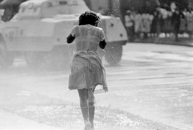A young black woman, soaked by a fireman's hose as an anti-segregation march is broken up by police, in Birmingham, Alabama, on May 8, 1963. In the background is a police riot wagon. (Photo by AP Photo)