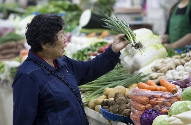 A customer selects vegetables at a market in Nanjing, Jiangsu province, China, October 14, 2015. Consumer inflation in China eased more than expected in September while producer prices fell for the 43rd straight month, adding to concerns over growing deflationary pressures in the world's second-largest economy. (Photo by Reuters/Stringer)