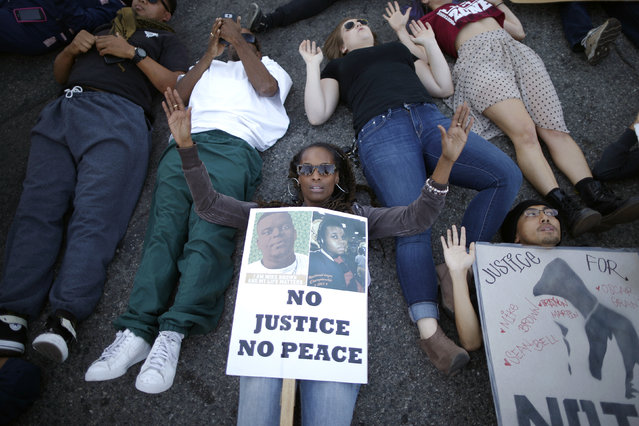Protesters lie in an intersection during a demonstration, following the Tuesday grand jury decision in the shooting of Michael Brown in Ferguson, Missouri, in Los Angeles, California November 25, 2014. U.S. President Barack Obama said on Tuesday anyone who destroys property in rioting against a Missouri grand jury's decision should be prosecuted, urging Americans upset by the court to work together to improve race relations. (REUTERS/Lucy Nicholson)