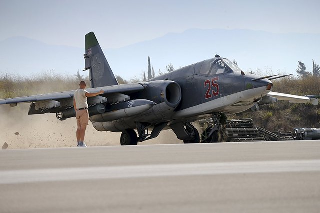 A Russian ground staff member signals to the pilot of a Sukhoi Su-25 fighter jet at the Hmeymim air base near Latakia, Syria, in this handout photograph released by Russia's Defence Ministry on October 22, 2015. (Photo by Reuters/Ministry of Defence of the Russian Federation)