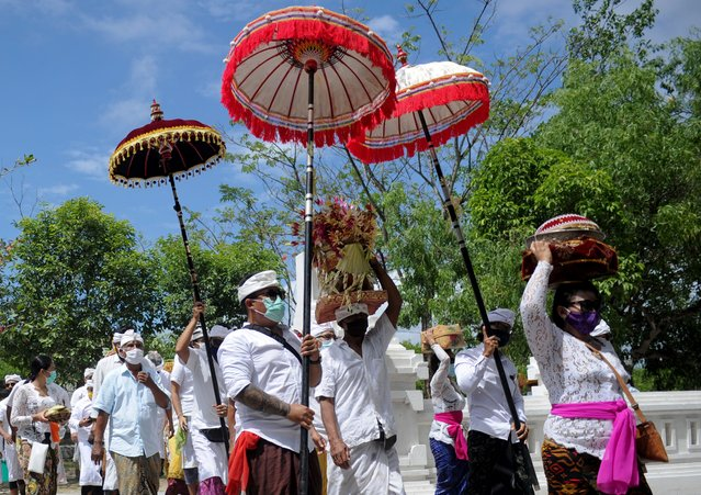 People carry offerings to pray during the religious festival of Kuningan, the last day of the Galungan celebrations believed to be the ascendent day of ancestral holy spirits returning to heaven, at Sakenan temple at Serangan island near Denpasar on the Indonesian resort island of Bali on September 26, 2020. (Photo by Sonny Tumbelaka/AFP Photo)