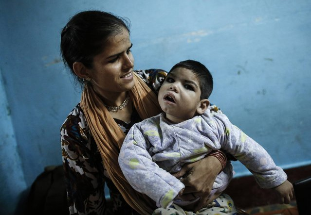 Three-year-old Abdul, who suffers from mental and physical disabilities plays with his mother Rukhsana at their house in Bhopal November 13, 2014. Abdul receives treatment at a rehabilitation centre supported by Bhopal Medical Appeal which only treats families they believe have been affected by the Union Carbide gas leak 30 years ago.(Photo by Danish Siddiqui/Reuters)