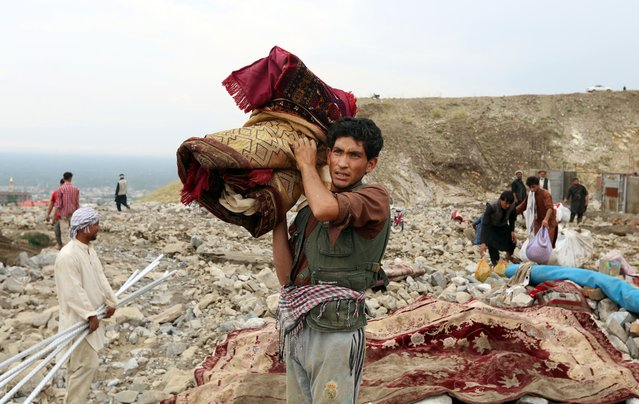 People collect belongings after a heavy flood in Charikar city of Parwan province, Afghanistan, 26 August 2020. According to local officials, at least 25 people were killed and dozens wounded in heavy floods on 26 August that also destroyed hundreds of houses and roads. (Photo by Jawad Jalali/EPA/EFE)