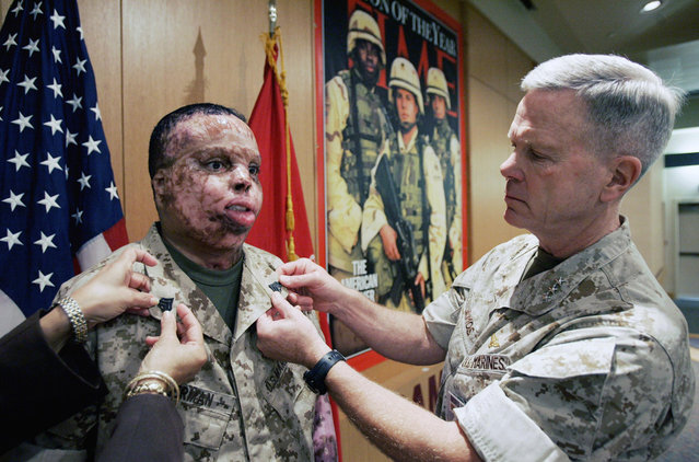 Marine Sgt. Merlin German (left) poses for photos with Lt. Gen. James F. Amos during German's promotion ceremony at Brooke Army Medical Center in San Antonio, on May 21, 2007. German was recovering from burns over 97 percent of his body caused by a roadside bomb in Iraq. He later died, in April of 2008, following a minor skin graft surgery. (Photo by Eric Gay/AP Photo/The Atlantic)